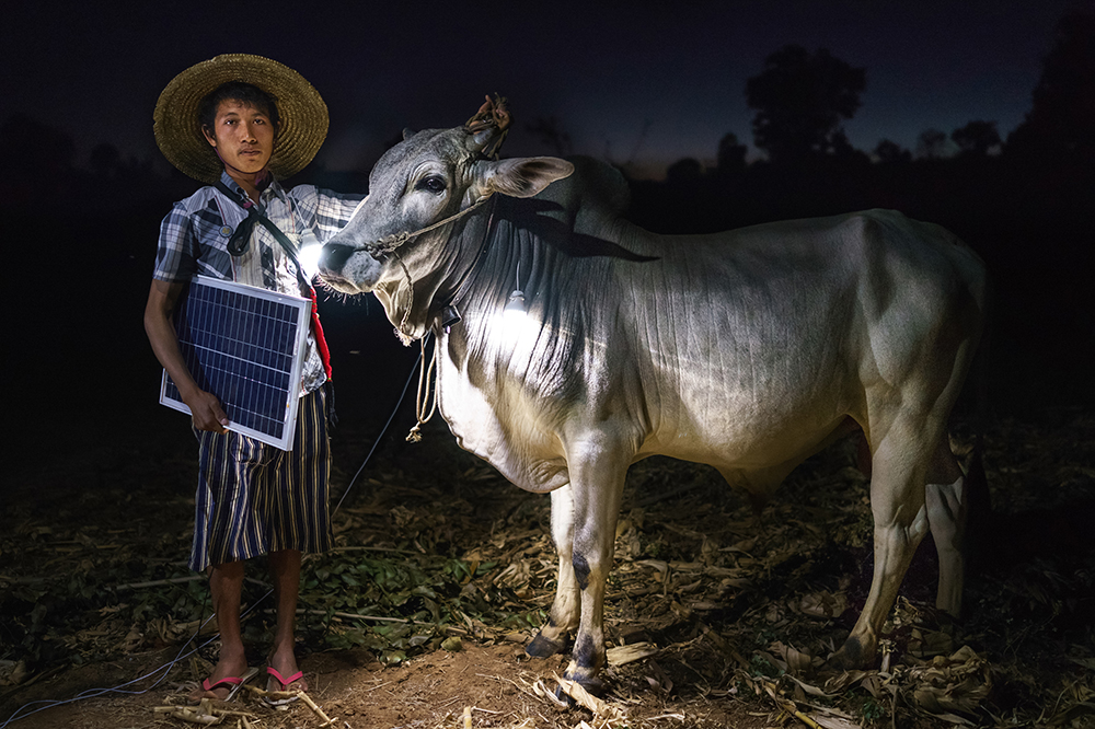 Mg Ko, 20 years old. A Shan farmer with his cow in Lui Pan Sone Village. Kayah State. Just 26% of Myanmar has access to electricity, at least half of whom live in cities. In rural areas, of the estimated 68,000 villages in the country, just 3,000 or so have any sort of access to power. Solar power is a viable source of energy which can rapidly improve lives overnight. The scenes have all been lit only by solar powered light bulbs which are contributing to the improvement in these people´s standard of living.