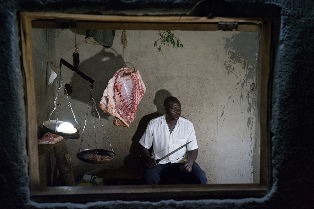 (May 31st, 2015) Butcher Mugerwa Lawrence (50) sits in his small shop at night where he sells meat until 1am in Kalagala, Uganda. Electricity is a rare luxury in Uganda. The portrait was set up using solar lights as the only source of ilumination.