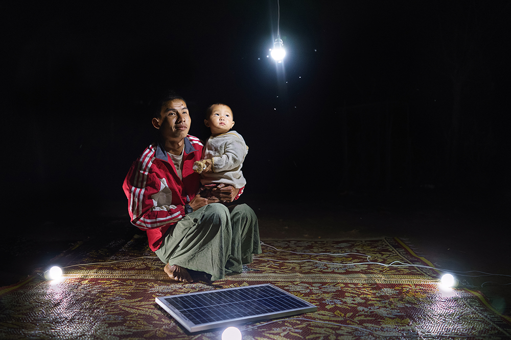 Ko Ba Aye, 26. and his 1 year old son Sai Kaung Htet Mon outside of their home in Lui Pan Sone Village. Kayah State. Just 26% of Myanmar has access to electricity, at least half of whom live in cities. In rural areas, of the estimated 68,000 villages in the country, just 3,000 or so have any sort of access to power. Solar power is a viable source of energy which can rapidly improve lives overnight. The scenes have all been lit only by solar powered light bulbs which are contributing to the improvement in these people´s standard of living.