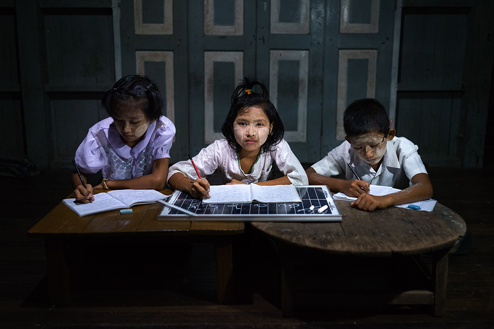 Grade 11 students do their homework in a solar-powered after-school community center near in Taman Chan Village, in Dala Township. Just 26% of Myanmar has access to electricity, at least half of whom live in cities. In rural areas, of the estimated 68,000 villages in the country, just 3,000 or so have any sort of access to power. Solar power is a viable source of energy which can rapidly improve lives overnight. The scenes have all been lit only by solar powered light bulbs which are contributing to the improvement in these people´s standard of living.