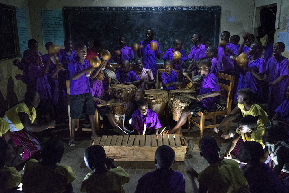 "(May 30th, 2015) Students rehearse ""Nankasa Bakisimba Muwogola"", a traditional Baganda music, at night after school for a yearly regional competition where different schools show off their musical skills in the Buganda District. Electricity is a rare luxury in Uganda so having solar lamps at this school has extended their studying hours. The portrait was set up using solar lights as the only source of ilumination."