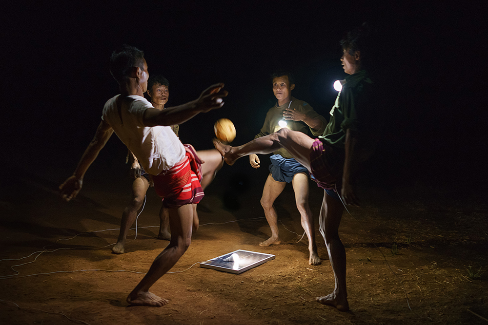 Men playing Chinlone, Myanmar's national sport on a field in Pa Dan Kho Village. Just 26% of Myanmar has access to electricity, at least half of whom live in cities. In rural areas, of the estimated 68,000 villages in the country, just 3,000 or so have any sort of access to power. Solar power is a viable source of energy which can rapidly improve lives overnight. The scenes have all been lit only by solar powered light bulbs which are contributing to the improvement in these people´s standard of living.