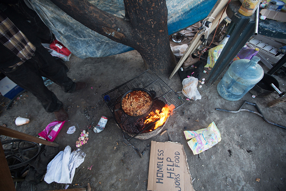Homeless farmworkers in Huron, CA, prepare a meal after recieving contributions solicited with the sign laying on the ground.