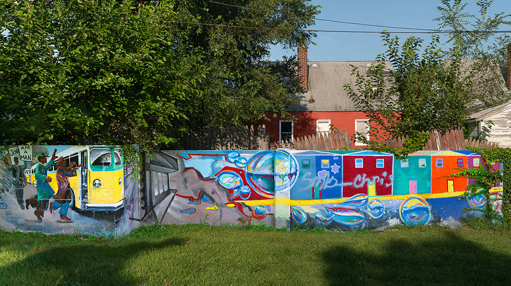 At six feet tall and one foot thick, the half-mile long wall was built to segregate a black community from an adjacent white development. It was never meant to physically separate people, but instead to do so legally and symbolically. It all started in 1934, when the Federal Housing Administration (FHA) was founded. The FHA signed into law the process of Òredlining,Ó the act of denying loans and financial services to black neighborhoods while granting them for white neighborhoods. This widened the economic gap between races to a whole new level. The neighborhood of Wyoming was a redlined black neighborhood for nearly a decade until the early 1940s, when developers wanted to build a white development in the area. They were denied by the FHA because their plan placed the white neighborhood Òtoo closeÓ to the black neighborhood. Thinking quickly, the developers responded by building a half-mile long wall directly in between Mendota Street and Birwood Avenue for a full three blocks. This was enough to be given the nod of approval from the U.S. government. The wall was the official racial divider for over 20 years, until the Fair Housing Act abolished such racist policies in 1968. The wall itself, however, still remains today Ñ as does segregation in Detroit. While both sides of the wall are currently black neighborhoods, the area around DetroitÕs Eight Mile Road is staunchly divided between the majority white north side and majority black south side. Although the wall doesnÕt run alongside Eight Mile Road, itÕs become known as the ÒEight Mile WallÓ as a reference to the modern-day epicenter of DetroitÕs segregation. (ItÕs also called the ÒWailing WallÓ or ÒBirwood Wall.Ó)  As a harsh reminder of the racial divisions of the past and the present, the Eight Mile Wall is yet to be knocked down. It remains a divider to this day Ñ albeit symbolically, not legally Ñ between adjacent backyards for three straight blocks. However, the wall has lost its blank white paint job and gotten a makeover. Over the years, it has been painted over with colorful murals, together sending a brighter message of unity, community, and progress.