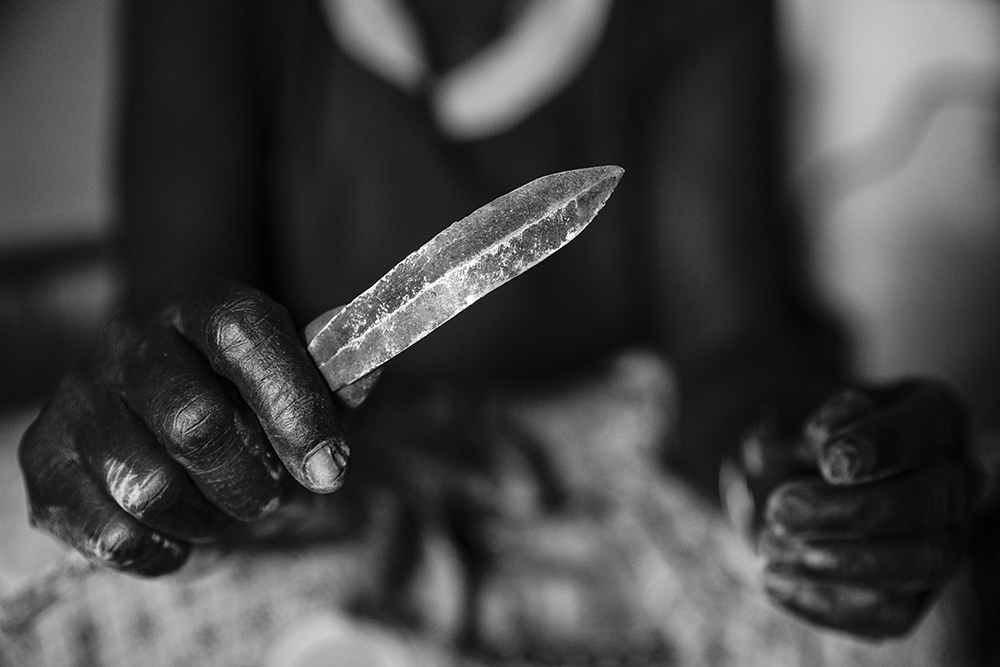 A woman that once performed female genital mutilation (FGM) holds the tool that she used to perform the FGM with in West Pokot, Kenya.