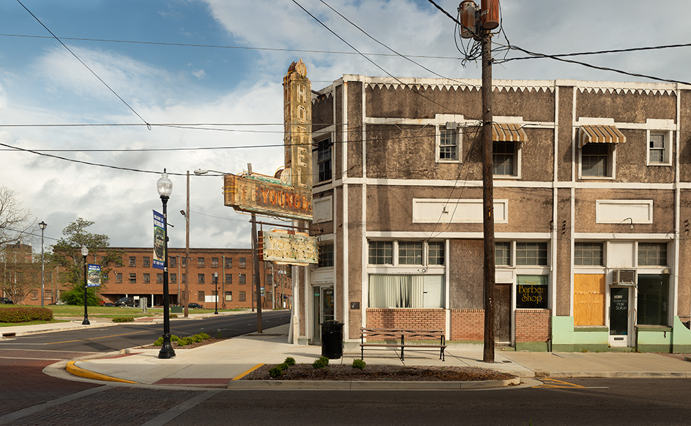 E.F. YOUNG HOTEL; Meridian, Mississippi 2018  E. F. Young Jr.'s hotel was one of two listings of accommodations for black travelers in Mississippi under the years of segregation and Jim Crow laws, listed in Victor Green's travel guide, The Green Book.   E. F. Young Jr. was born in 1898 the son of a farmer and eventually became one of the wealthiest African American businessmen in the Southeast. He started as a barber as a young man, experience he used to formulate his own hair care products. On February 14, 1933, he registered the E. F. Young Jr. Manufacturing Company – the first ethnic hair care product manufacturer in the United States – with the U.S. Patent Office. It quickly became one of the largest African-American owned companies in the South. In 1946, Young realized his final goal in the establishment of his commercial empire. That year he opened his own barber and beauty shop, as well as the first and only Meridian hotel to serve African Americans. He called his new establishment the E. F. Young Jr. Hotel. YOUNG HAD LONG BEEN involved in the struggle for Civil Rights in Meridian. During the 1940s, he served as the Vice President of Meridian's Chapter of the NAACP. By 1942, Young had helped recruit nearly one hundred dues paying members. Even after E. F. Young Jr. died in 1950, his business establishments continued to serve Meridian's African American community. Following Young's death in 1950, family members continued to operate his various businesses. In 1953, his wife and three children renewed his patent for E. F. Young Manufacturing Co. Through the 1960s, the E. F. Young Jr. Hotel remained the only Meridian hotel to serve black patrons, and in a 1962 issue of Ebony Magazine, Young's hotel was the only lodging listed in the state of Mississippi. As one of the only African-American hotels in the state, the E. F. Young Jr. Hotel welcomed a long list of distinguished guests, including Leontyne Price, Ella Fitzgerald, the Harlem Globetrotters, and Martin Luther King, Jr. The E. F. Young Jr. hotel remained in operation until 1978, when the building was rented to office tenants. In recent years it has lain entirely vacant. ©Rich Frishman ALL RIGHTS RESERVED