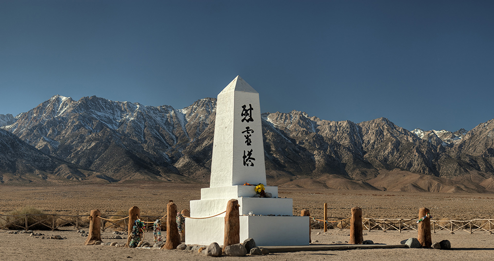 "Manzanar is most widely known as the site of one of ten American concentration camps where over 110,000 Japanese Americans were unjustly incarcerated during World War II from December 1942 to 1945. Located at the foot of the Sierra Nevada in California's Owens Valley between the towns of Lone Pine to the south and Independence to the north, it is approximately 230 miles (370 km) north of Los Angeles. Over 135 Japanese internees died during their incarceration at Manzanar. Their ashes were buried in this small cemetery outside the barbed wire perimeter. In 1943 some of the Japanese prisoners built this obelisk. The inscription translates as ""Monument to comfort the souls of the dead."" The famous white obelisk, the Soul Consoling Tower, is one of the few remaining structures from the Manzanar concentration camp and the cemetery it marks is where the annual Manzanar Pilgrimage is held each year on the last Saturday in April."