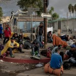 A group of migrants wait before being transferred to a different temporary shelter in Tijuana, Mexico on November 30, 2018. Mexican officials required all the migrants to leave the Benito Juarez encampment due to safety and hygienic concerns and move instead to the outskirts of Tijuana to the El Barretal complex.  Photo by Kitra Cahana / MAPS
