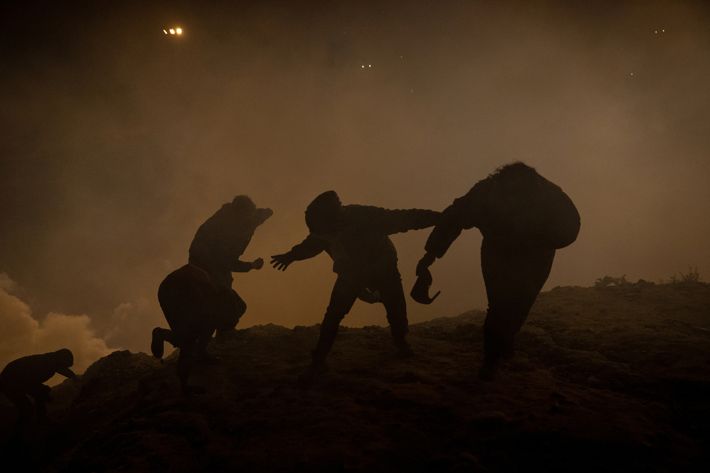 Migrants, journalists and U.S. activists run from tear gas on January 1, 2019 after US authorities fired tear gas over the border wall in Tijuana, Mexico. A group of approximately 150 migrants attempted to cross the border but their attempt was thwarted when CBP discovered where they were hiding and used several crowd control techniques to disperse the group. Photo by Kitra Cahana / MAPS