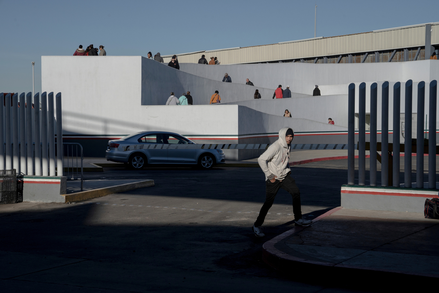 A migrant whose numbers was called waits to board a van that will bring him and his family to US immigration authorities where they will present their cases for asylum at the Chaparral pedestrian crossing on the US-Mexican border in Tijuana, Mexico on December 8, 2018.  Migrants return daily to the plaza by the crossing to see if their number is called from the list 'La Lista', a self-organized, migrant-run system that determines who gets to present their cases to US immigration authorities each day. Photo by Kitra Cahana / MAPS