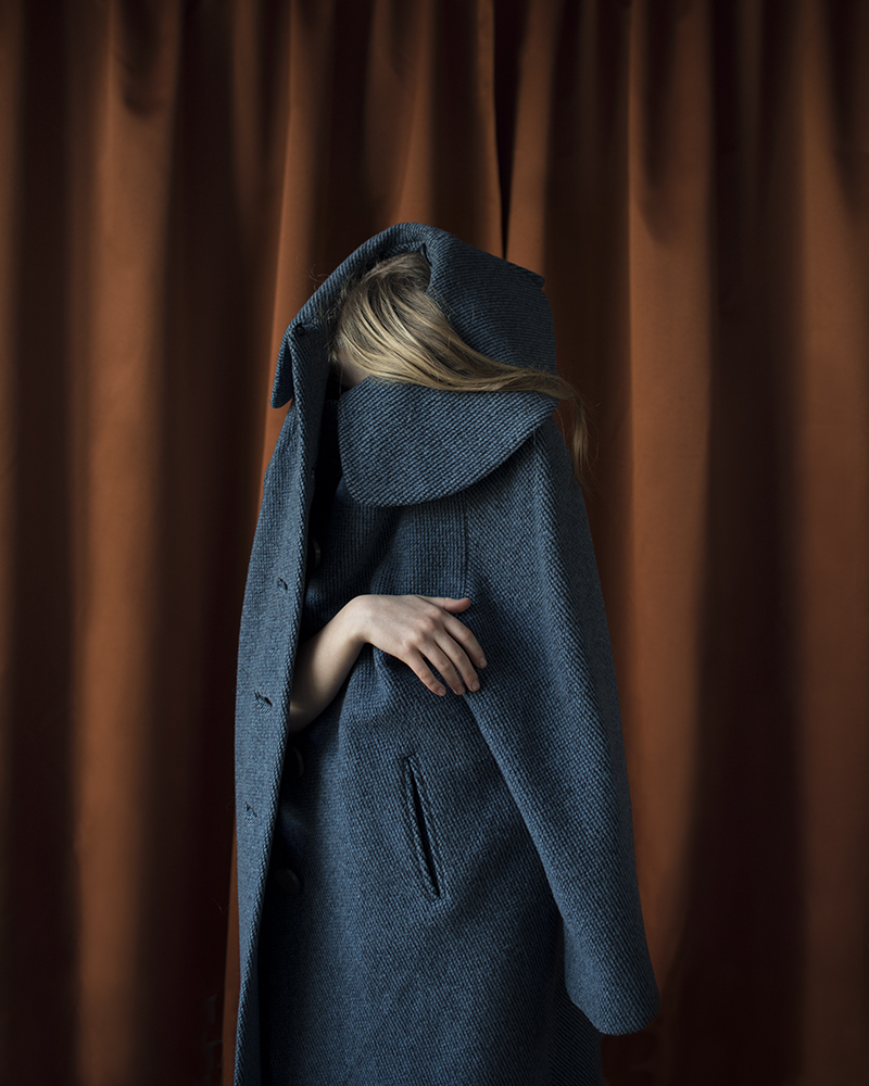 girl hiding in large coat