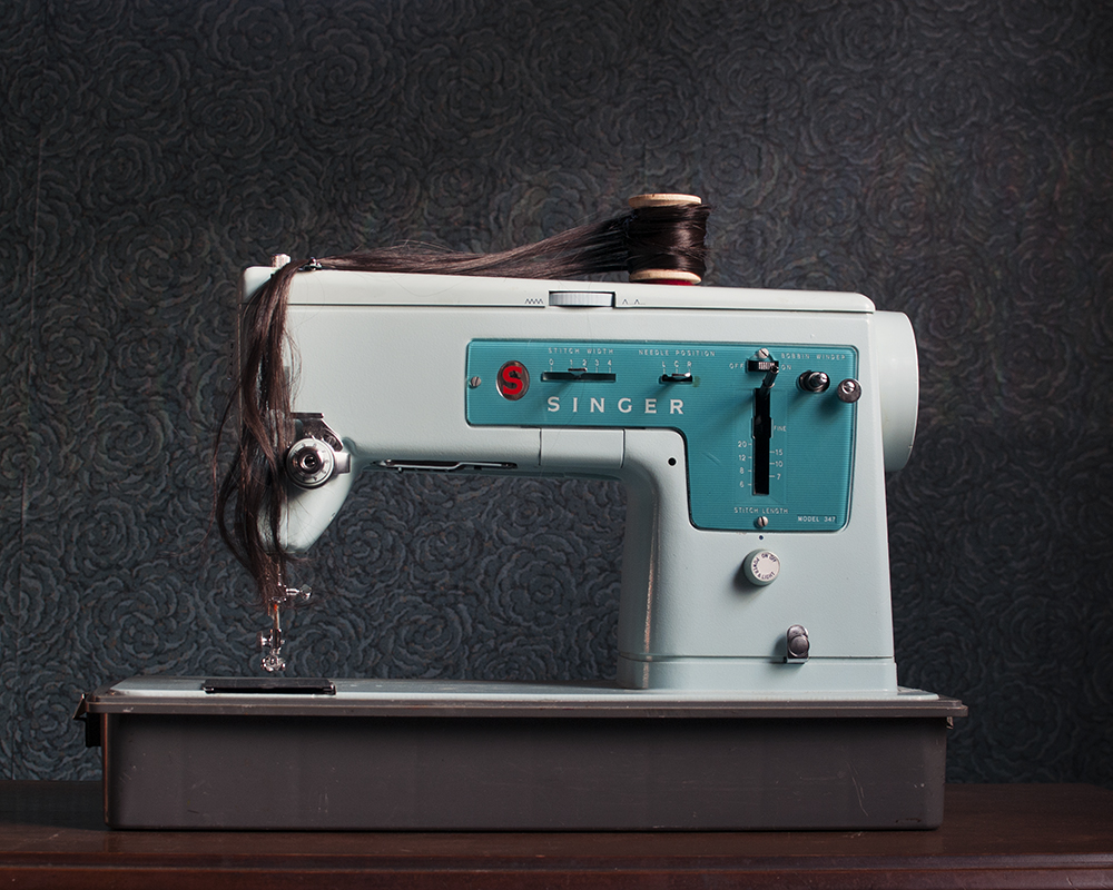 Vintage blue sewing machine with hair threaded through