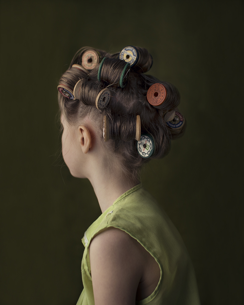 young girl with hair in thread spool rollers - green background