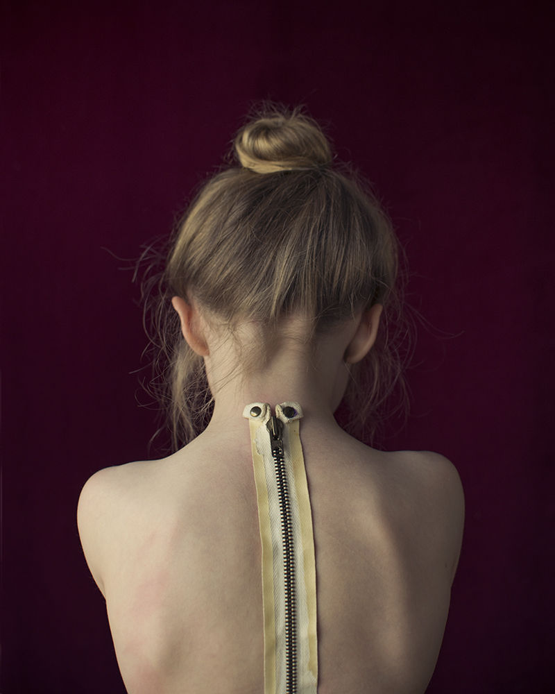 young girl with zipper on spine