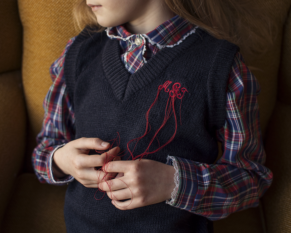 young girl in stringy monogram vest