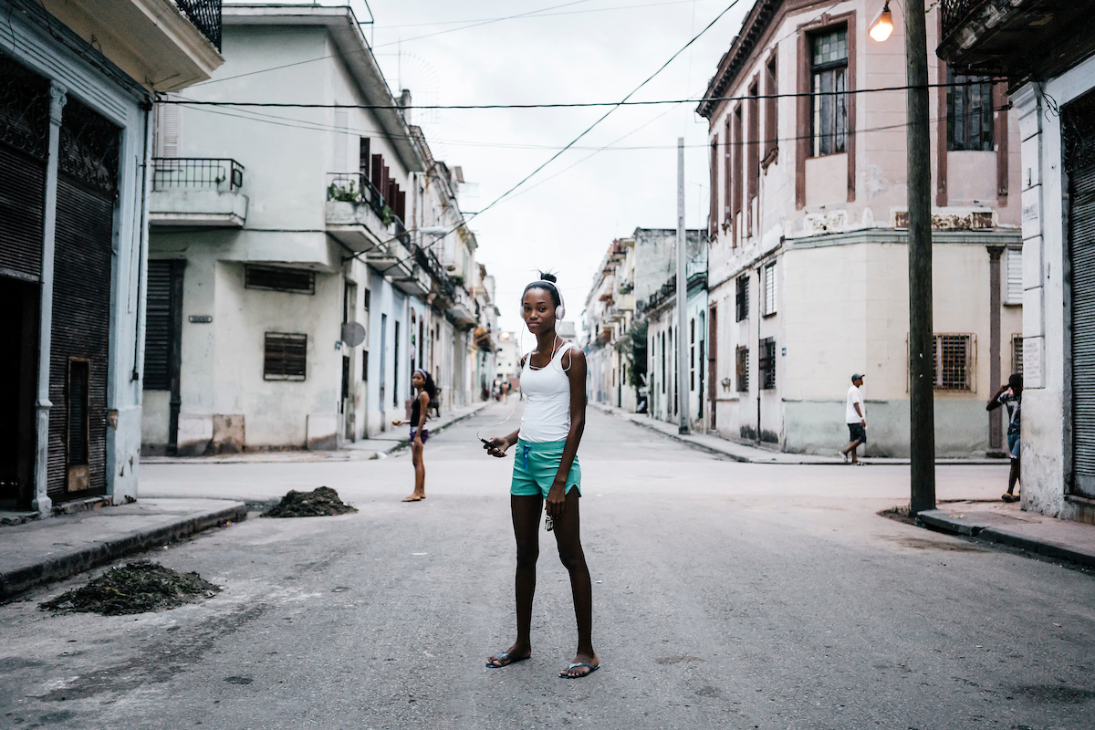 Anna Marie Mesa, 16, listens to music on her smartphone in Centro Havana. Technology is leapfrogging the infastructure in Cuba where citizens went from landlines to smartphones in a matter of months. Cubans born after 1989 have only known a time after the USSR dissolved and left the Caribbean nation with little resources and a powerful, growth-crippling, US-led economic embargo.