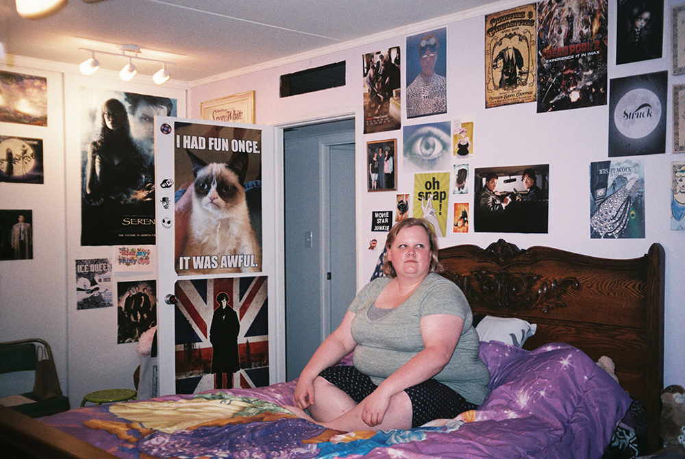 Lauren H. photographed in her bedroom at the home she shares with one of her best friends. Lauren works as a drama and English teacher at the high school next door to her home.