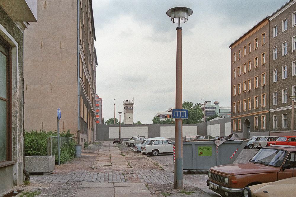 Durch die Hinterlandmauer abgeschnittene Strelitzer Straße (damals nach einem erschossenen DDR-Grenz-Posten benannt: Egon-Schultz-Straße) in Berlin Mitte (ehemals Berlin - Hauptstadt der DDR). Im Vordergrund Ostberliner Straßenszene mit Wohnhäusern aus der Gründerzeit, Straßenlaternen, geparkten Pkws und einem Sperrmüllcontainer. Im Hintergrund Mauer mit Wachturm, dahinter drei Gebäude an der Bernauer Straße in Berlin Wedding (ehemals Westberlin). Blickrichtung Nordwesten.