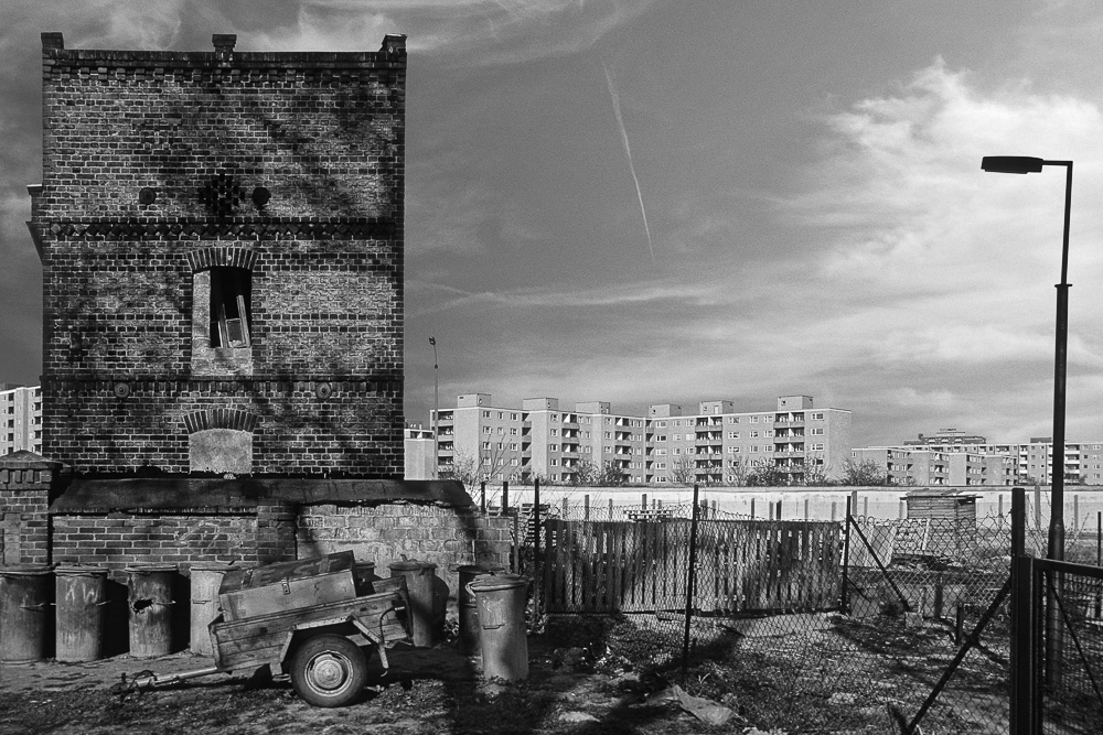 Berliner Mauer in Höhe des Staakener Nennhauser Dammes (DDR / Bezirk Potsdam) und dem Zweiwinkelweg (Spandau/ Westberlin). Im Vordergrund alte Remise aus Ziegelmauerwerk auf einem Grundstück in der DDR. Im Hintergrund Todestreifen mit Mauer vor Neubaublöcken in Spandau Neu-Staaken. Blickrichtung Osten