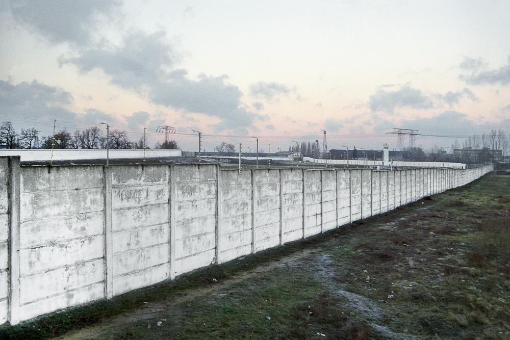 Blick über die Hinterlandmauer an der Rudower Chaussee in Berlin Köpenick (Berlin - Hauptstadt der DDR) hinweg zum Teltowkanal, der hier im Todesstreifen verläuft. Heute (seit 2004): Autobahntrasse A 113 am Ernst-Ruska-Ufer. Links im Hintergrund: Äußere Grenzmauer an der Köpenicker Straße in Berlin Neukölln (Westberlin), rechts im Hintergrund: Wachturm, Verlauf der Hinterlandmauer entlang des früheren Flugplatzgeländes Johannisthal. Blickrichtung Nordwesten.