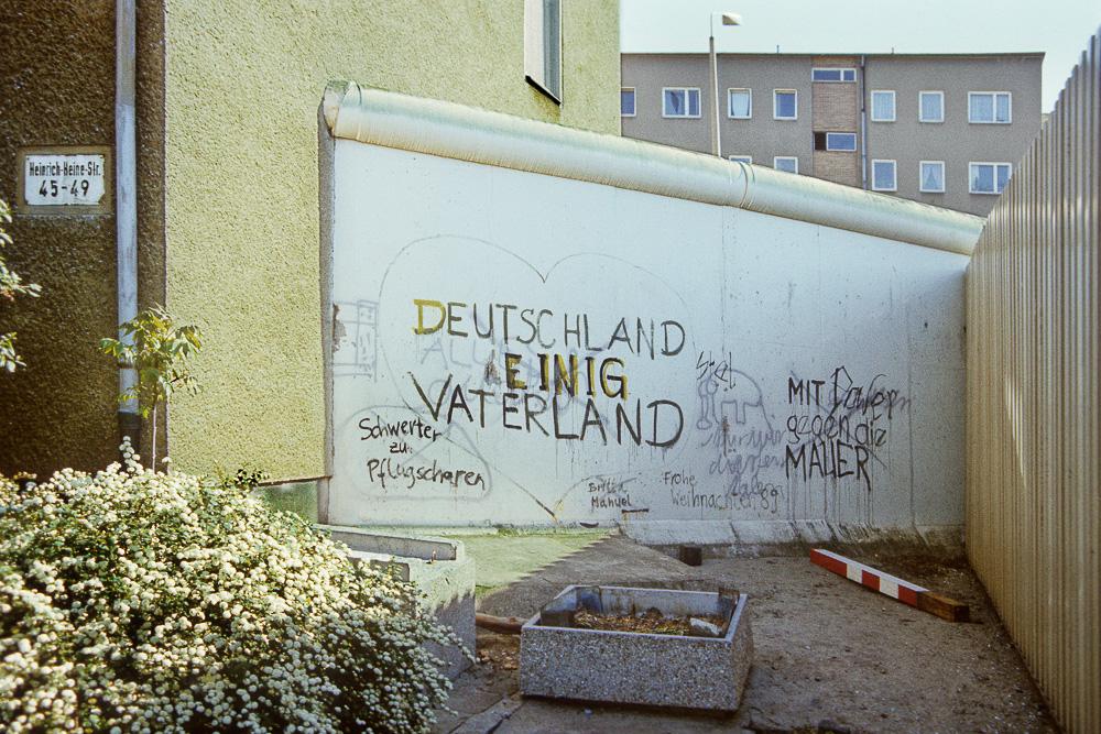 """Versatzstück der Hinterlandmauer mit Graffity """"Deutschland einig Vaterland"""" im östlichen Bereich des Kontrollpunktes Heinrich-Heine-Straße. Links Wohnblock in der Heinrich-Heine-Straße in Berlin Mitte (Berlin-Hauptstadt der DDR), dahinter Wohnblock in der Sebastianstraße in Berlin Kreuzberg (Westberlin). Blickrichtung Südwesten."""