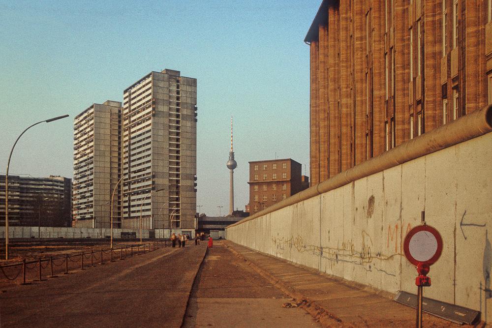 Todesstreifen auf der Lindenstraße in Berlin Kreuzberg (Westberlin), im Hintergrund Fernsehturm, Rotes Rathaus und Hochhäuser an der Leipziger Straße in Berlin Mitte (Berlin-Hauptstadt der DDR), Blickrichtung Nordosten.
