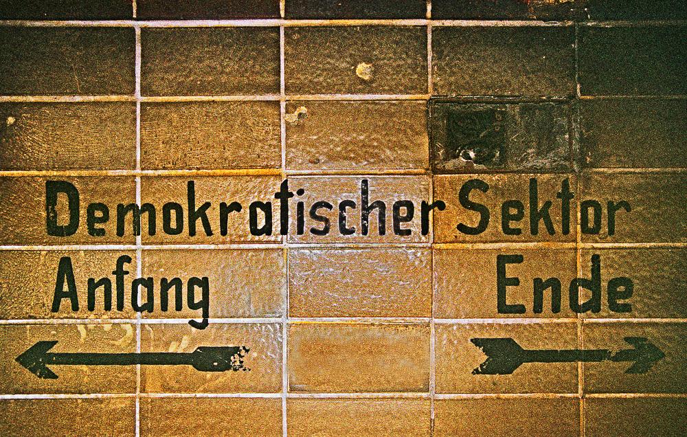 """Aufgrund der Ostberliner Grenzbefestigung seit dem 13. 8. 1961 ungenutzter unterirdischer S-Bahnhof """"Nordbahnhof"""", Architekt: Reichsbahnoberrat Lüttich. Schriftzug der Ostberliner Administration im Fußgängertunnel von der nördlichen Verteilerhalle zum Bahnhofsausgang in der Gartenstraße, die teilweise zu Westberlin gehörte. """"Demokratischer Sektor"""" bezeichnet paradoxerweise den Ostteil Berlins."""