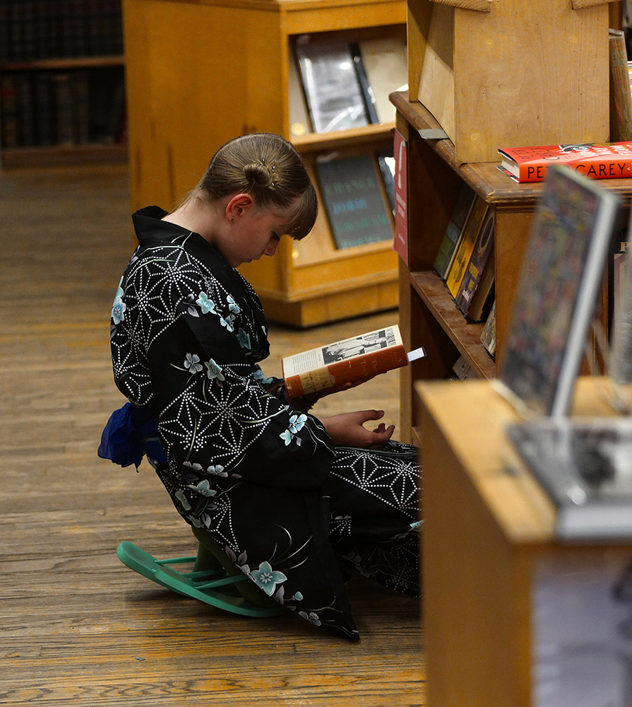 Reading Series—The Art of Reading..Young girl in Kimona reading in the Rare Book Room of the Strand Bookstore in NYC. Exclusive photo by Lawrence Schwartzwald