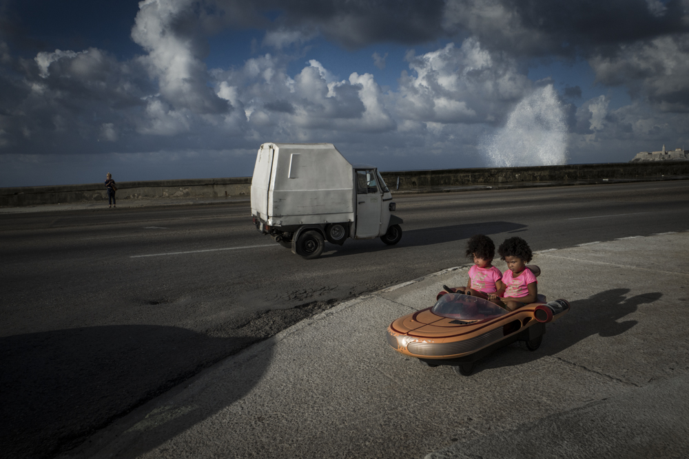 Cuba / Havana/ 2019 / On the mythical Malecón Avenue and seawall, these young twin sisters struggle to follow their father who took them along while jogging and ran out of the frame. Due to the collapse of Venezuela and the Trump administration's tightening of the decades-old embargo on Cuba, September 2019 was marked by fuel shortages all over the island nation and the roads were even emptier than usually. © Marylise Vigneau / Anzenberger