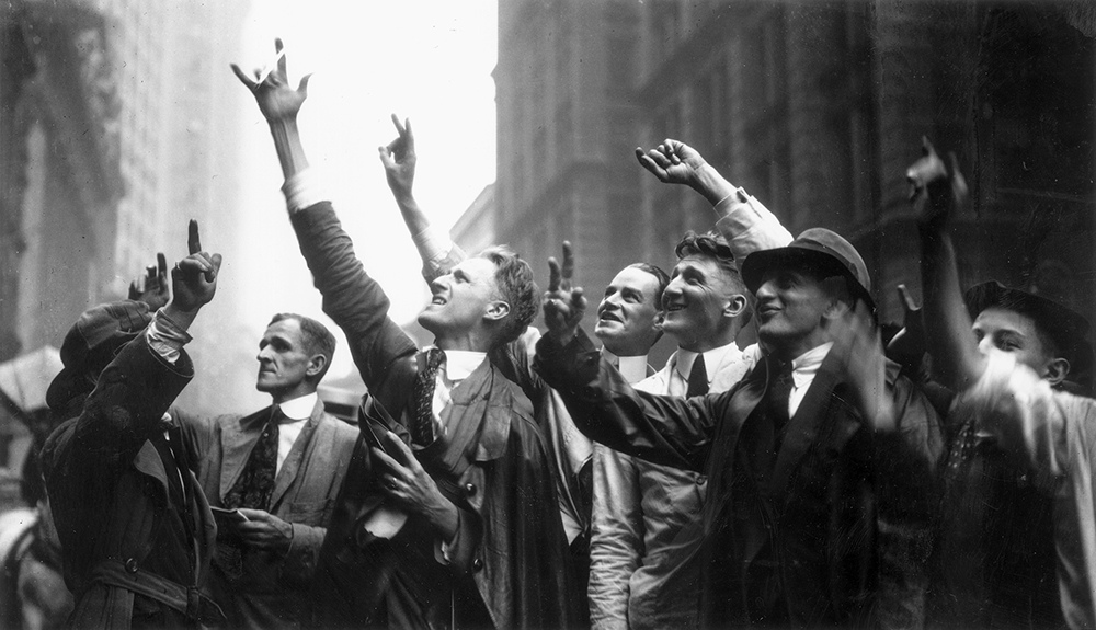 circa 1925:  Curb Market traders gesture with their hands to trade stocks, on Wall Street, New York City. The Curb Market was for stocks not listed on the New York Stock Exchange.  (Photo by Hulton Archive/Getty Images)