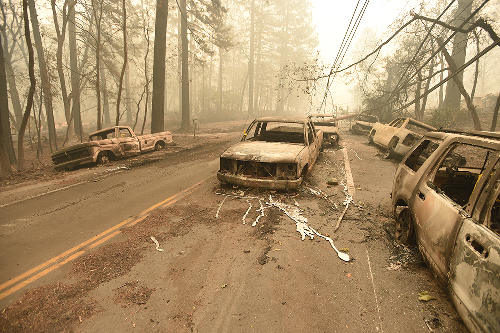 Abandoned burned out vehicles are seen on the side of the road in Paradise, California after the Camp fire tore through the area on November 10, 2018.