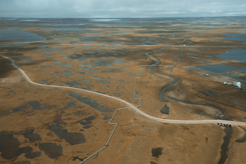 An access road outside of Prudhoe Bay, Alaska intersects a set of pipelines. Seemingly insignificant oil support infrastructure can alter the dynamic of the relatively flat and featureless tundra in surprising ways because of the sheer unbroken length of roads and pipelines.