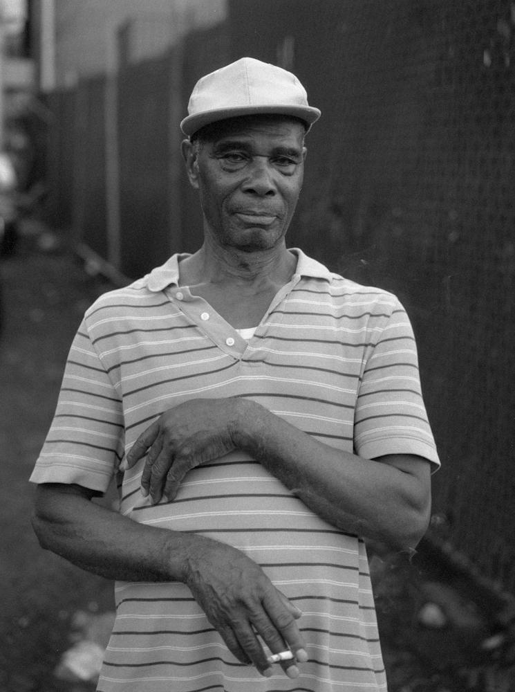 A Haitian man smokes a cigarette