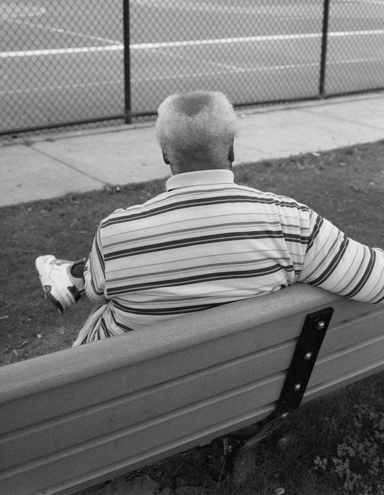 A man who lives across the street sits on a bench and watches on