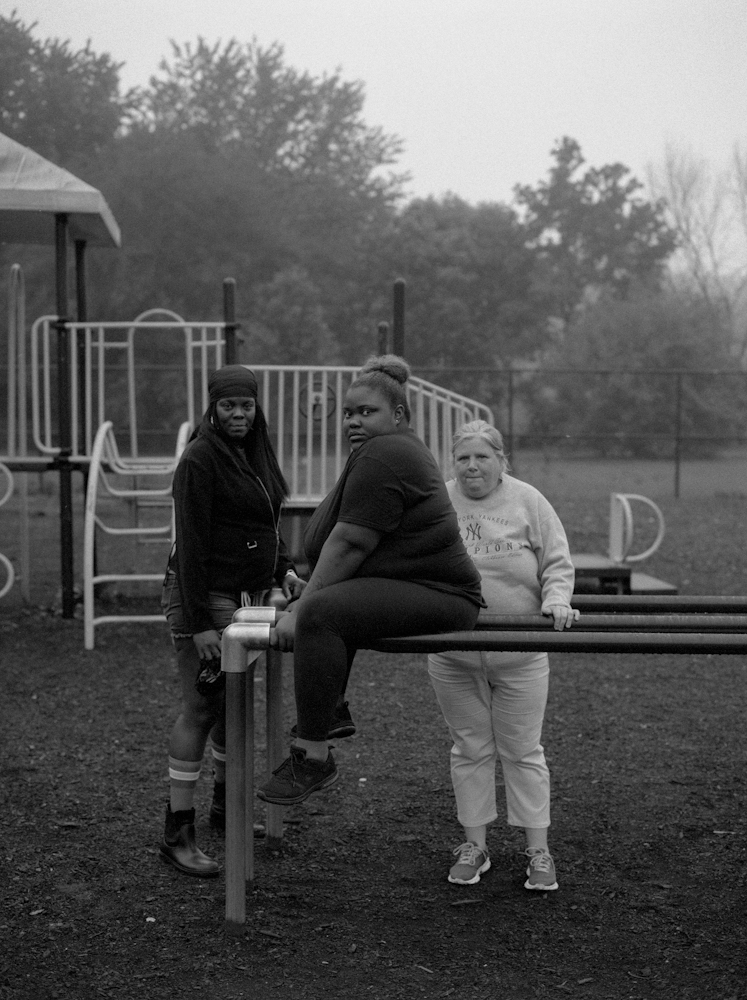 Three friends stands inside of a children's playground located in the park