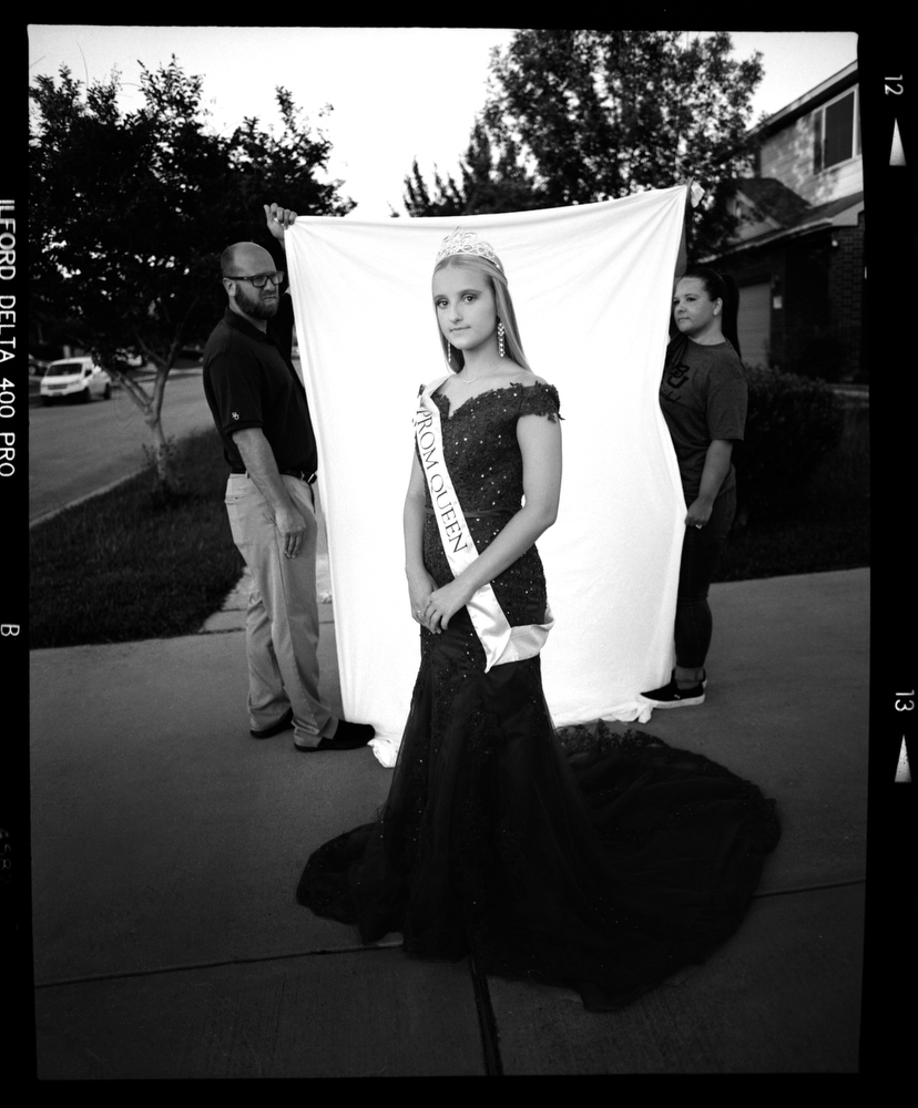 "Faith Dearing, 18, wears her sister's prom queen sash along with the dress she planned on wearing to prom before it was cancelled due to COVID-19 concerns as her mother and father drapes a backdrop behind her on Wednesday, May 6, 2020 in Killeen, Tx. ""For two years I waited to run for prom queen to fulfill what my sister did when she was in high school but now I won't be able to,"" Dearing said. [Image produced on 120 film using a Pentax 6x7 Medium Format Film Camera]"
