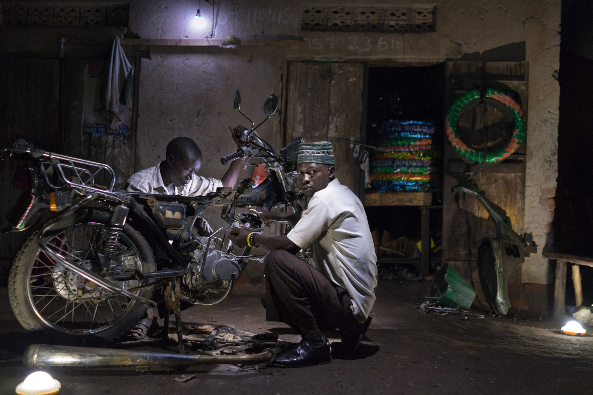 Ibrahim Kalungi and Godfrey Mteza, both 20, work at night in their motorcycle repair shop in Nbeeda, Uganda. The mechanics credit solar lights with enabling them to work longer hours and earn more money. Electricity is a rare luxury in Uganda.