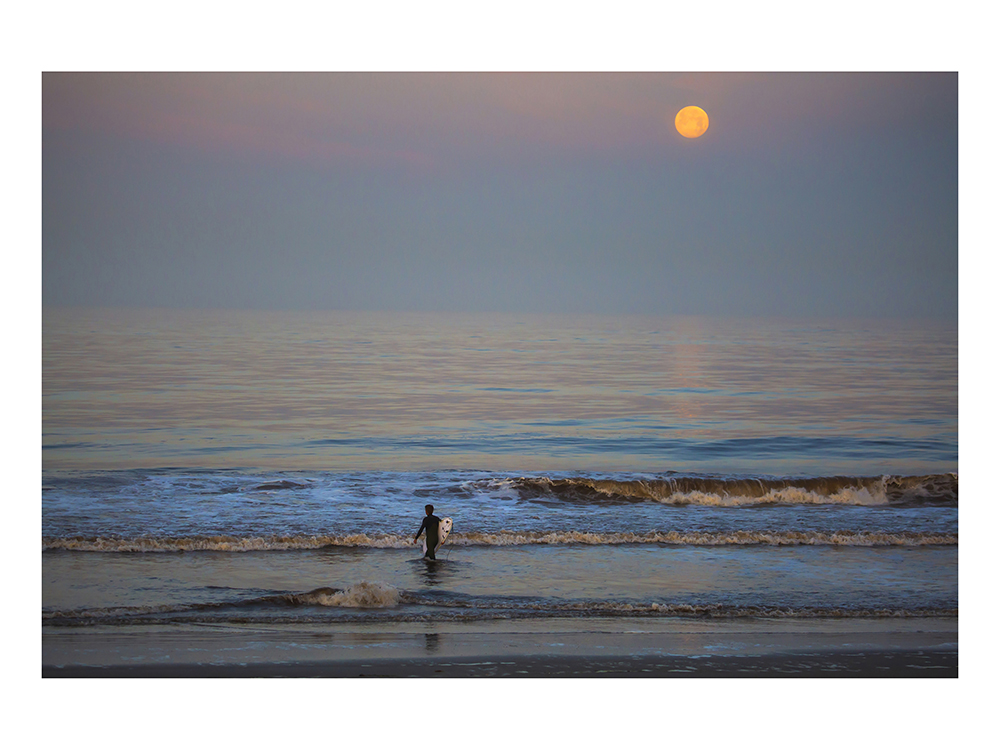 A surfer takes to the ocean at sunrise under the super moon, May 7, 2020.  Photo by Karen Ballard