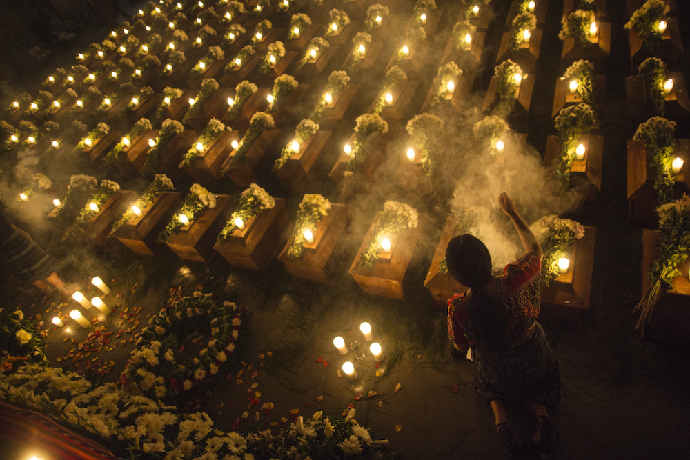 In this June 20, 2018 photo, a woman burns incense on the coffins with the remains of 172 people exhumed in a former military regiment in San Juan Comalapa, Guatemala. In a small town in Guatemala some of the 45,000 thousand disappeared during the civil war will now be able to rest in peace. The women of Comalapa, located in the department of Chimaltenango some 77 kilometers west of the Guatemalan capital, created a place to pay the missing from the war from 1960 to 1996 the tribute that the State has denied despite a request in that sense of the Inter-American Court of Human Rights. (AP Photo/Rodrigo Abd)