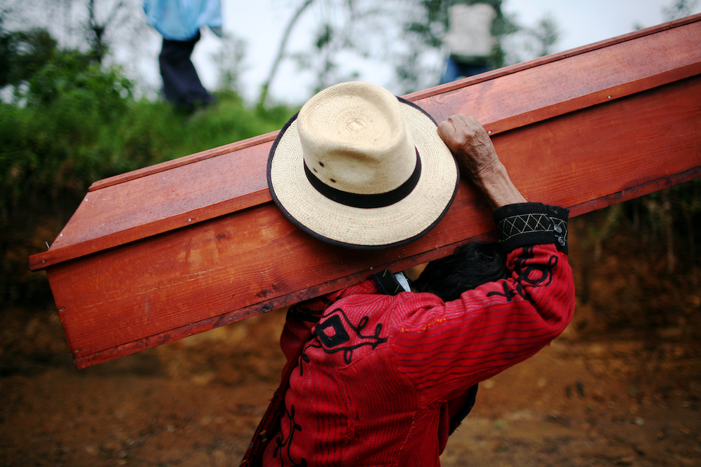 A man carries a coffin of a villager killed during a massacre made by the Guatemalan Army in 1981, Cocop, Nebaj, around 300 km northwest from Guatemala City, Tuesday, June 10, 2008. After the exhumation of 76 villagers killed April 16, 1981, in Cocop, Nebaj, a forensic antropologists team made a cientific study of the bones and clothes of the massacred villagers in order to identified them. After more than 2 years of study, the antroprologists are giving the remains to their relatives, do they can make a burial in the comunity. During the 36 years of civil war in the country, around 250.000 people were killed or dissapeared.(AP Photo/Rodrigo Abd)