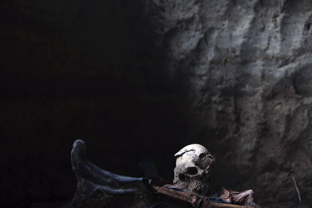 The skeletons of two of nine men who were tortured and massacred allegedly with the Guatemalan Army during the civil war are seen in a mass grave in Uspantan, Quiche, Monday, August 3, 2009.  Forensic anthropologists have begun to use DNA sampling and analysis to identify victims of human rights abuses committed during this country's 36-year-long civil war that left 200.000 dead and 40.000 disappeared.