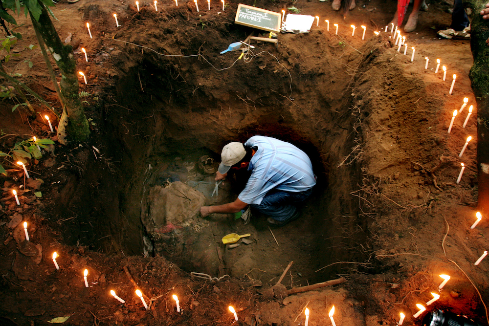 A forensic antrophologist works to exhume the body peasant killed by the army in 1982 during  the civil war , Chucalibal, Quiche, , 130 kilometers west of Guatemala City, Tuesday, May 17, 2005.  The Guatemalan Foundation for Forensic Anthropology oversaw the exhumation which was visited by family members of victims of violence from around the world, including relatives of victims of the September 11 attacks in the US. (Ap Photo/Rodrigo Abd)