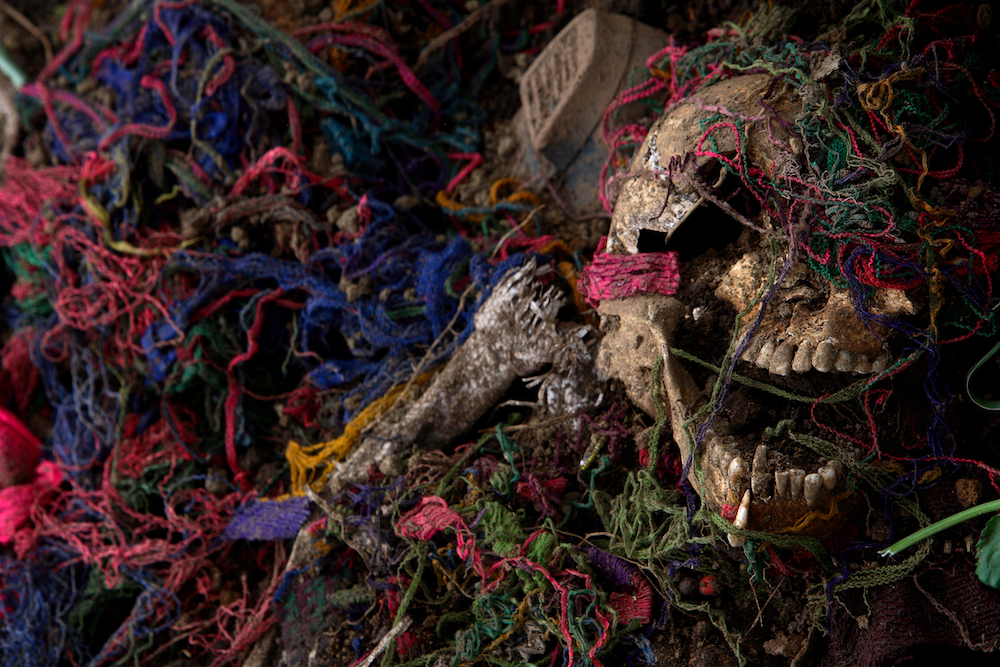 """A skeleton is seen next to indigenous clothes at  a mass grave where 12 persons were buried after being massacred by the Guatemalan  army in 1982 in """"El Adelanto"""" village, Solola, Guatemala, Friday, Aug 31, 2007.  Forensic antrophologists try to recover the remains of some 20 persons murdered, but 8 of them will not be exhumed yet because the owners of the lands where they were buried want to wait until they pick their corn crops before allowing the  exhumkation work of the antrophologists. During the Guatemalan Civil war, more than 200.000 people were killed or dissapeared. (AP Photo/Rodrigo Abd)"""