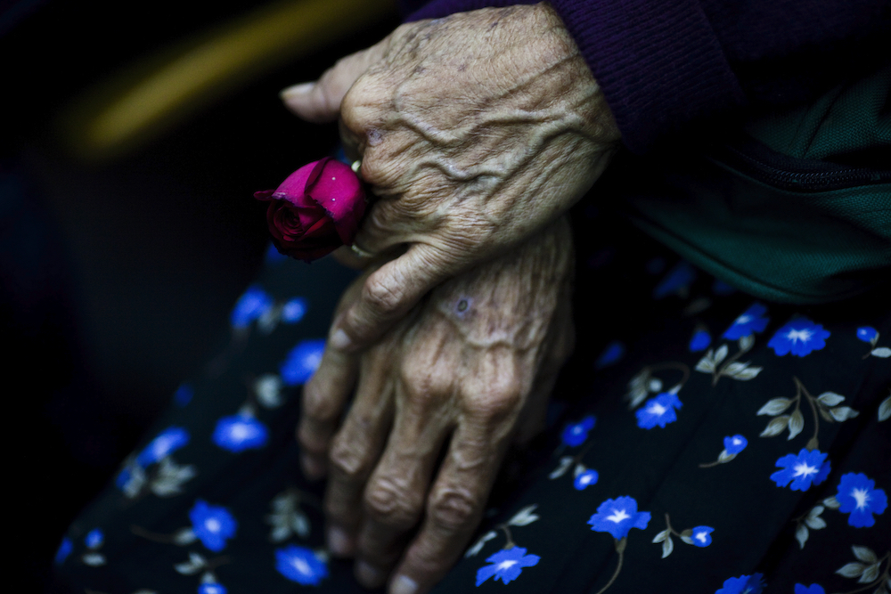 """Cristina Alfaro Mejia, whose husband and daughter were killed by soldiers during Las Dos Erres massacre in 1982,  holds a rose as waiting to the sentence in Guatemala City, Tuesday, Aug. 2, 2011. Four military officers were sentenced to 6,060 years in prison for being involved in the 1982 Las Dos Erres massacre that resulted in the killing of more than 200 people as part of a """"scorched earth"""" effort to eliminate communities supporting insurgent groups during the height of Guatemala's 36-year civil war. (AP Photo/Rodrigo Abd)"""