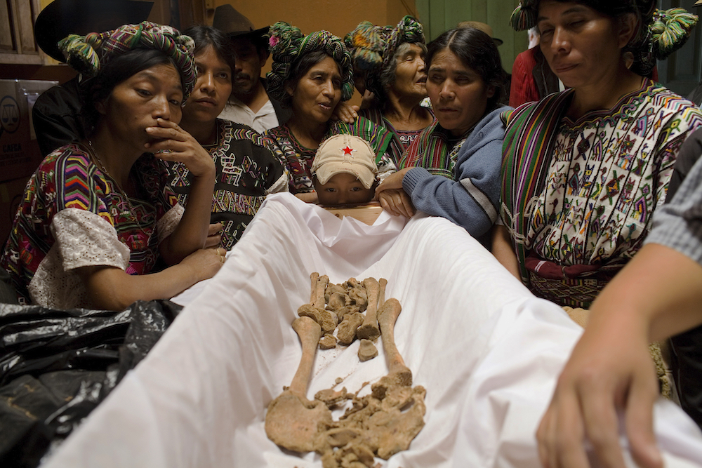 Relatives look to the bones of Gaspar Terraza Matom, around 10 years old, who was killed during a massacre made by the Guatemalan Army in 1981, Nebaj, around 300 km northwest from Guatemala City, Monday, June 9, 2008. After the exhumation of 76 villagers killed April 16, 1981, in Cocop, Nebaj, a forensic antropologists team made a cientific study of the bones and clothes of the massacred villagers in order to identified them. After more than 2 years of study, the antroprologists are giving the remains to their relatives, do they can make a burial in the comunity. During the 36 years of civil war in the country, around 250.000 people were killed or dissapeared.(AP Photo/Rodrigo Abd)