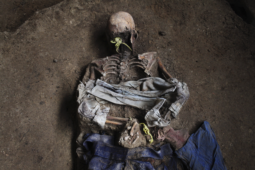 The skeleton of one of nine men who were tortured and masacred allegedly with the Guatemalan Army during the civil war is seen in a mass grave in Uspantan, Quiche, Monday, August 3, 2009.  Forensic anthropologists have begun to use DNA sampling and analysis to identify victims of human rights abuses committed during this country's 36-year-long civil war that left 200.000 dead and 40.000 disappeared. (AP Photo/Rodrigo Abd)
