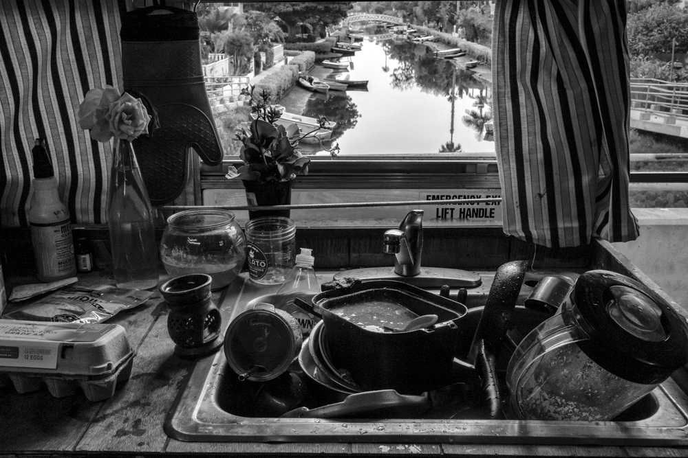 The reality of a kitchen sink overflowing with dishes merges with the dreamy background of the Venice Canals.