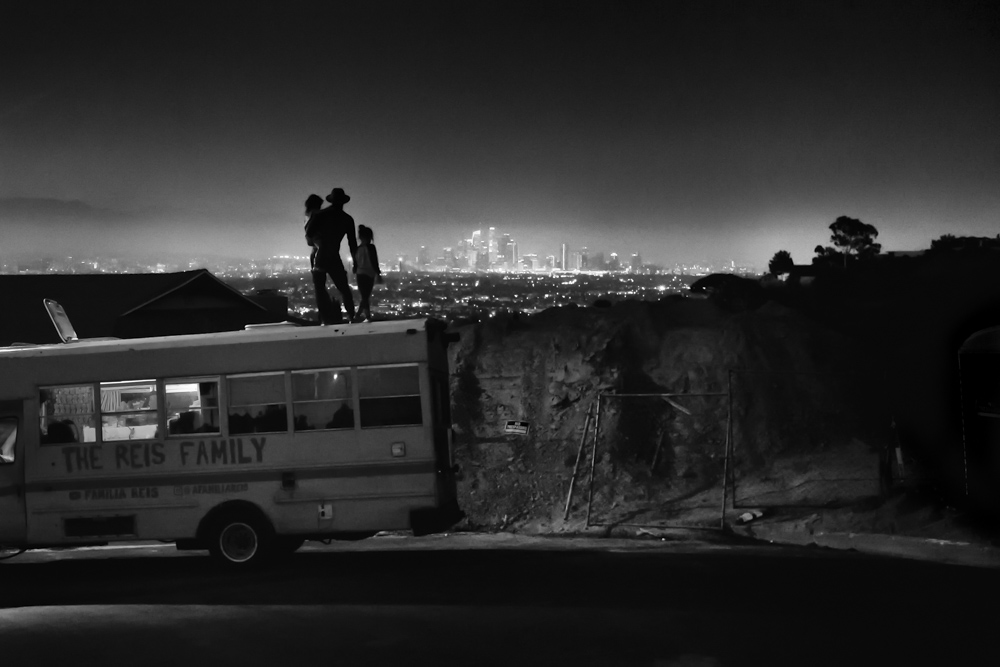 Izzy and his two daughters enjoy the view from the top of the family bus as the the Los Angeles city lights flicker below.