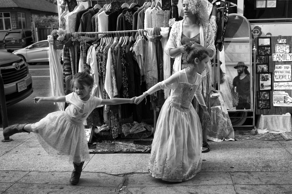 6-year-old Flor drags her 3-year-old sister Lua by the hand as they play in front of their parents' improvised vintage clothing display on Venice's popular Abbott Kinney Boulevard.
