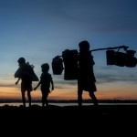 Rohingya children carry all of their belongings as they flee violence in their burned village in Myanmar and travel to refugee camps in Bangladesh.